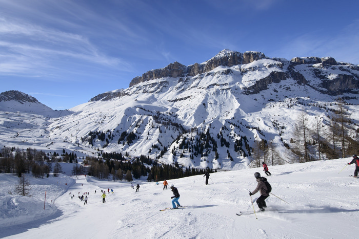 Arabba descending toward Pordoi pass, Arabba; skiers on bright snow over steep ski run in Dolomites in important ski area shutterstock_137391659.jpg